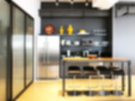 Agency Sack's pantry area with yellow accents, a steel refridgerator, a wooden bar table, and black leather stool. Designed by Lenart Architecture.