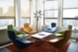 Bernstein Real Estate casual meeting space with colorful chairs to add a playful vibrance to the office.