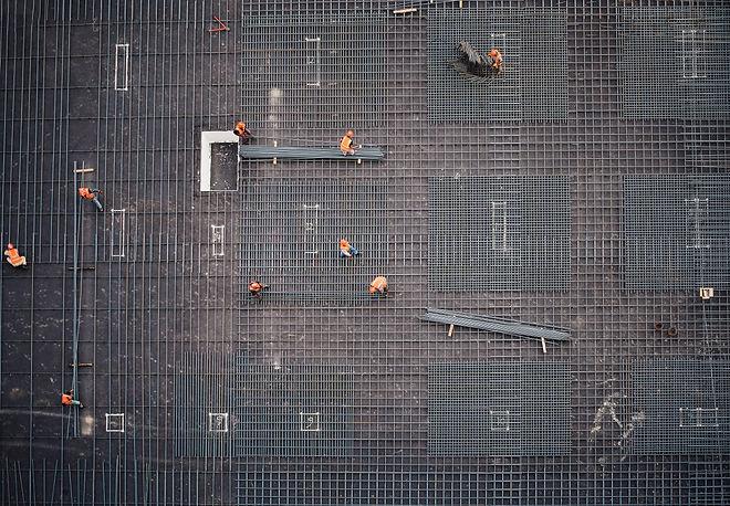 Hintergrundbild Stimmungsbild. Bauarbeitende am Verlegen von Armierungseisen für einen Betonsockel