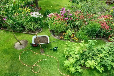 tuin met kruiwagen, schop en tuinslang