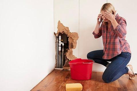 vrouw met een burst-waterpijp bellen voor hulp