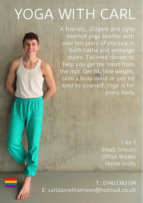 Yoga Instructor standing against a wall. He is wearing teal trousers and a white vest and has a friendly smile