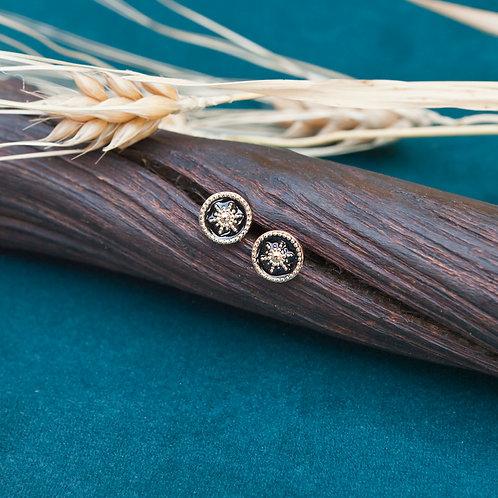 boucles d'oreilles puces rondes en plaqué or avec un solei lau centre sur fond émaillé noir