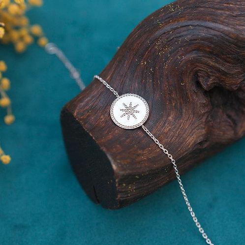 bracelet fin pour femme en argen avec une pastille ronde et une étoile en relief à l'intérieur