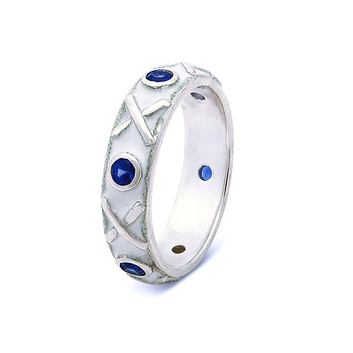 White enamelled silver eternity ring with blue sapphires