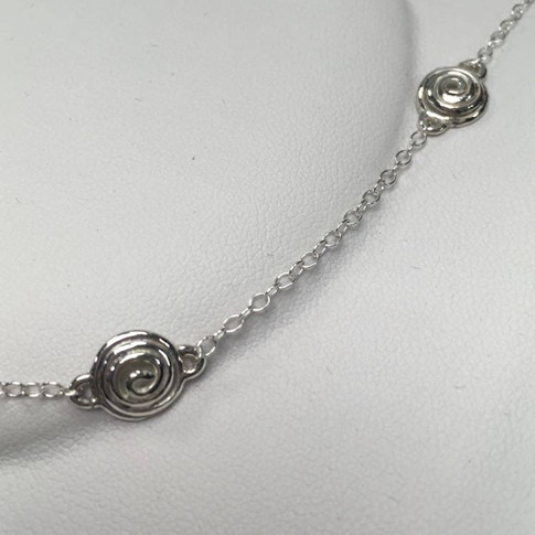 Close up of swirl necklace inspired by snails
