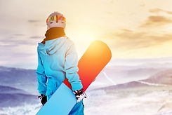 Girl snowboarder stands with snowboard o