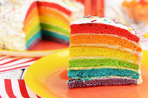 Delicious rainbow cake on plate on table