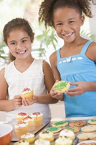 Two Children In Kitchen Decorating Cooki