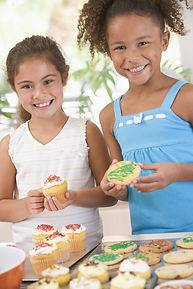 Two Children In Kitchen Decorating Cooki