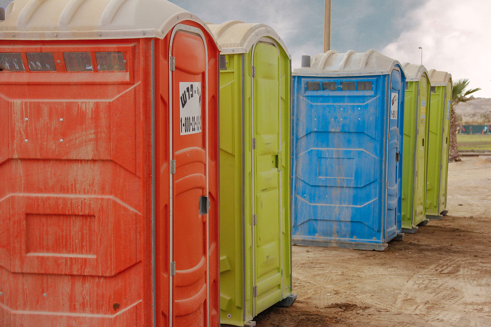 Image is a group of brigtly colored and weathered portable toilets arranged in a row on dirt outdoors.