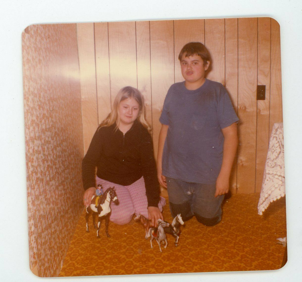 A blonde caucasian girl plays with toy horses while a brunette boy kneels beside her, super jealous of her awesome horses. They are dressed in 70's attire and in a 70's decorated room.