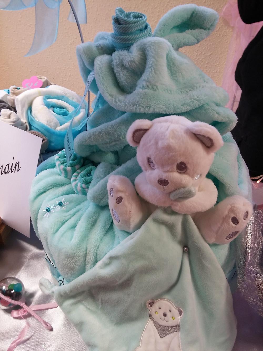 gateau de couches avec un doudou ours et une couverture