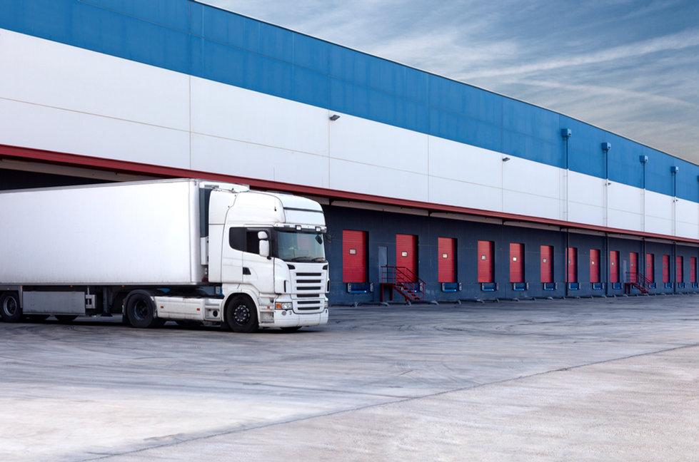 Logistikkonsult - Sim Logistics - Många portar och en vit lastbil vid en lagerlokal.
