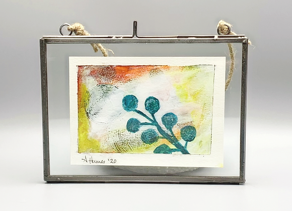 Small metal frame with abstract painting floating between two sheets of glass.