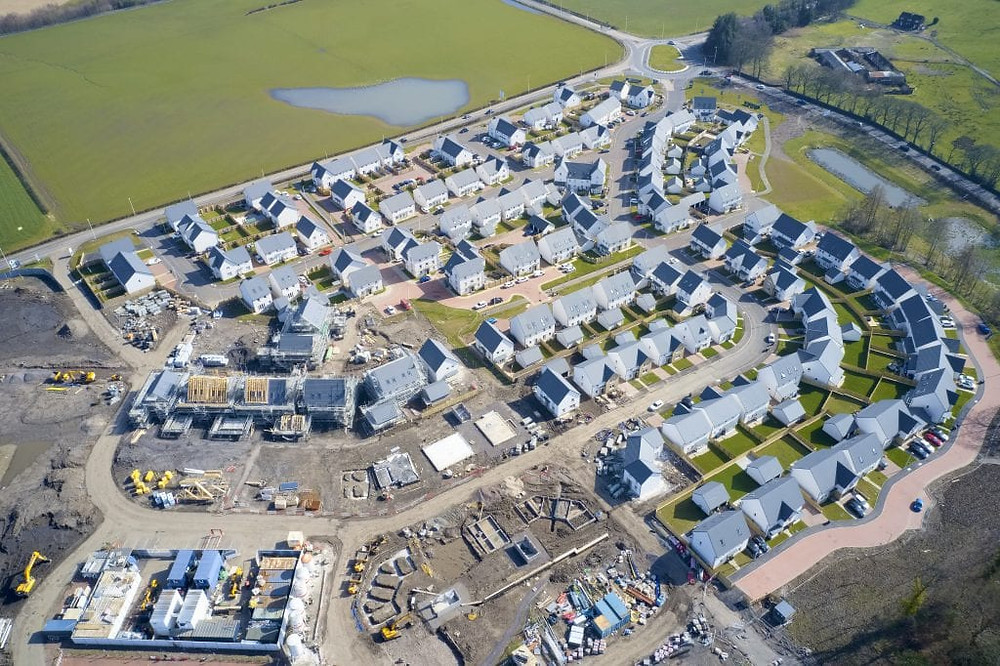 Suburban house development aerial view with countryside views uk