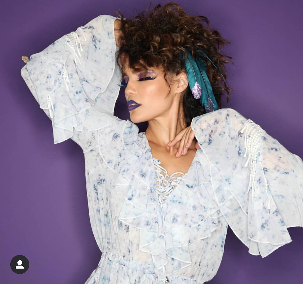 Model showcasing Kimberly Irene's avante garde look with teal feathers in her hair and a purple background