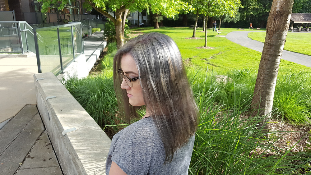 Young woman with the grey hair look that transitions into warm brown