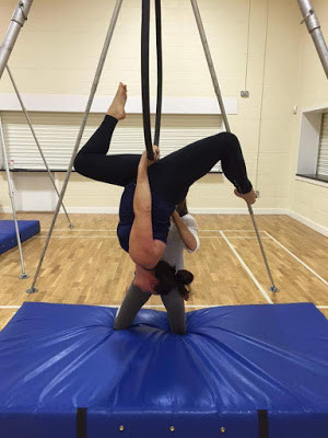 Jodie Golby performing an aerial hoop move at a workshop with Angela Hawkes at Pole Passion Bognor - Bersted Park