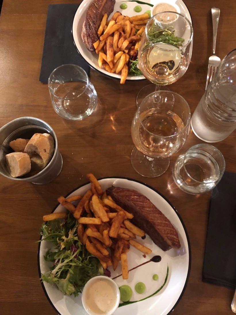 Pièces de canard, frites et salade, pain en accompagnement et rosé en boisson