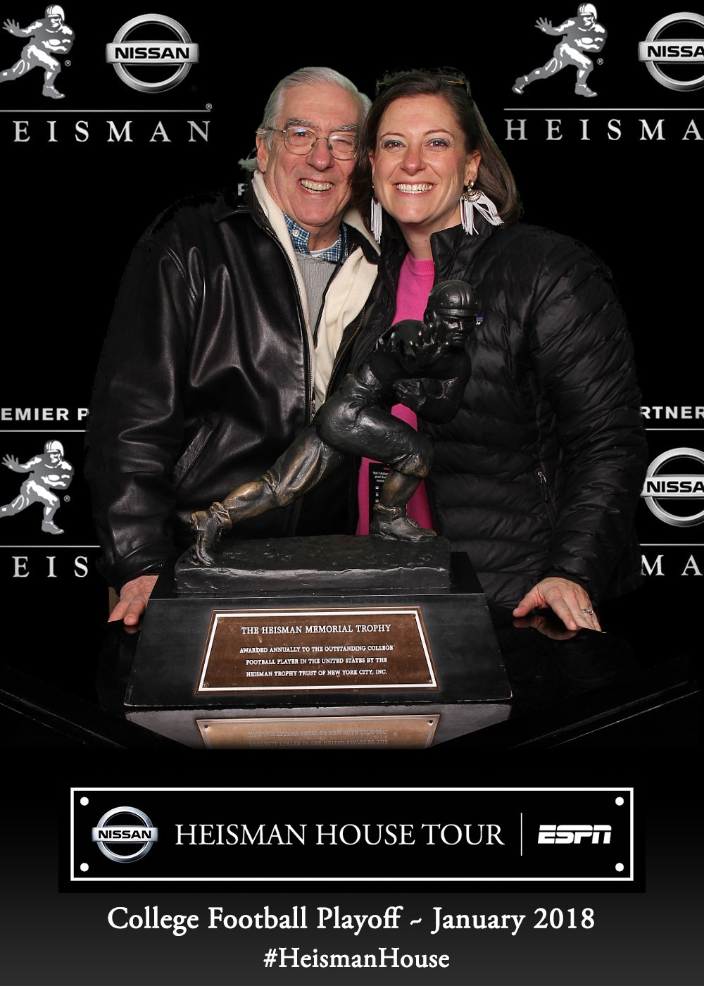 Tom Oder and daughter Olivia Banks with the Heisman Trophy at the Heisman House at the Fan Appreciation at the College Football Playoff experience outside Mercedes-Benz Stadium.