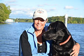 Sporty woman with black lab on dock on Long Lake