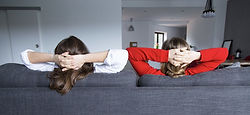 rear-view-female-roommates-relaxing-couc