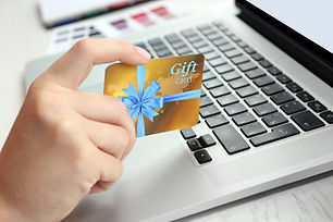 Woman with gift card and laptop, closeup