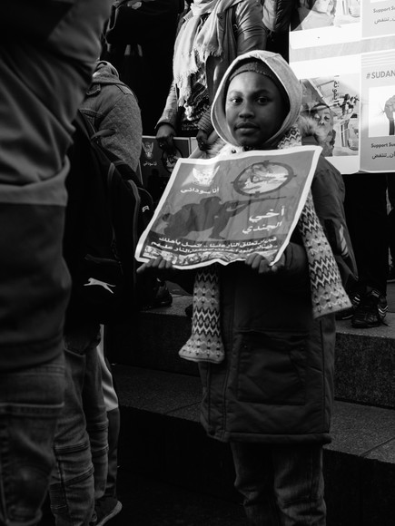 Child holds sign at #sudan-revolts Newcastle Upon Tyne Street Photography