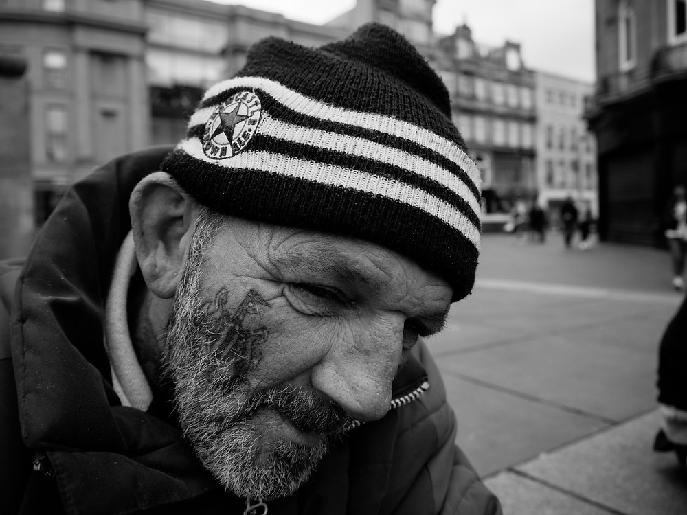 As soon as I saw the face tattoo I knew it was important for me to grab this shot. After speaking for a while, buying him a coffee, i was able to get this shot matching his hat, with his face, and his heart in the city.