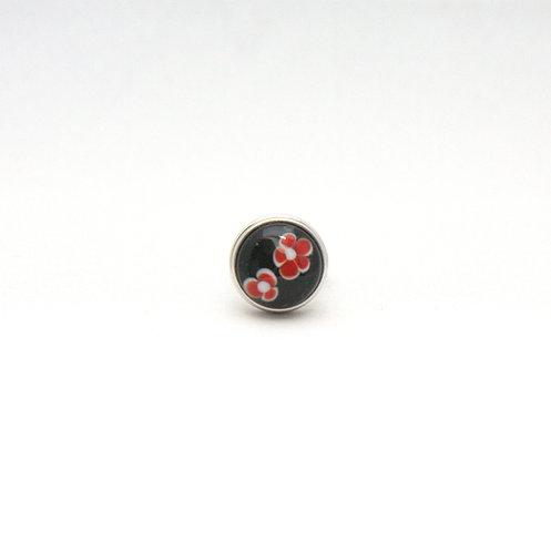 pression avec cabochon à fleurs rouges sur fond noir