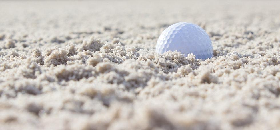 Golf ball in bunker sand.