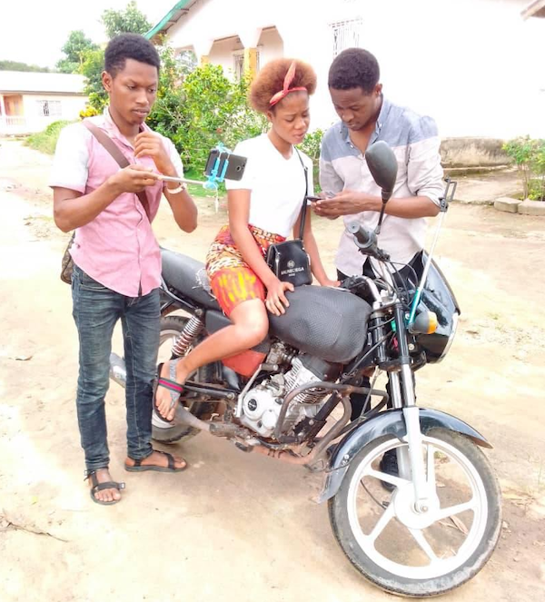 One female on a motorcycle looking at the phone a Male is showing her. While another male appears to take a picture with their mobile phone on a selfie stick.