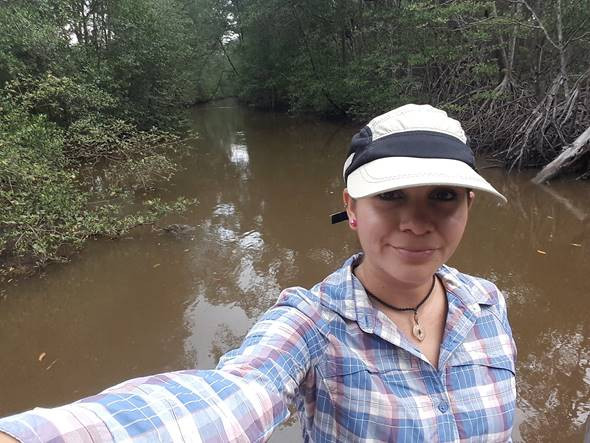 Selfie of Cristina in a blue flannel shirt with a hat on, posing in a wetland.