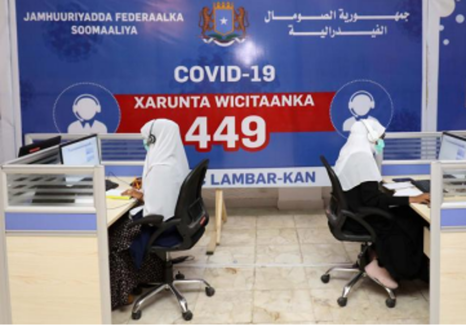 Two women sitting at desks looking at computers with a COVID-19 sign on the wall.