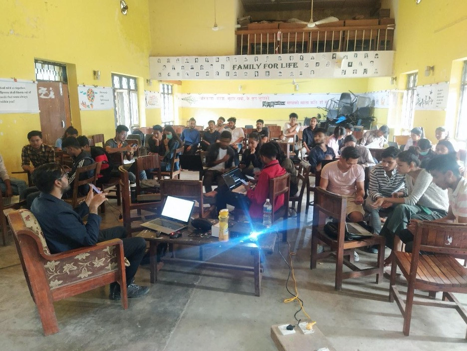Classroom with large group of students in small groups. There appears to be a presentation happening at the front of the room.