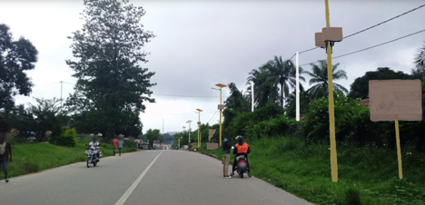 Photo taken on a rode with several pedestrians walking or on motorcycles. Along the road are light poles and trees.