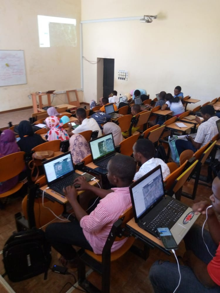 18 students picture in a classroom sitting at their desks, many are on computers with aerial imagery showing.