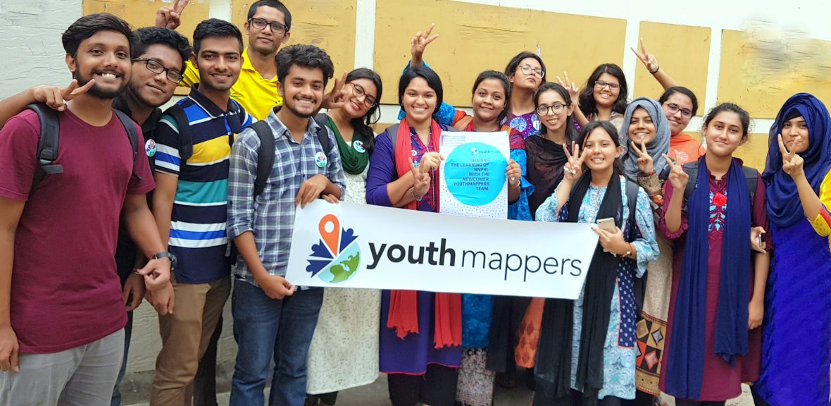Group of happy students(male and female) holding YouthMappers sign making peace signs.