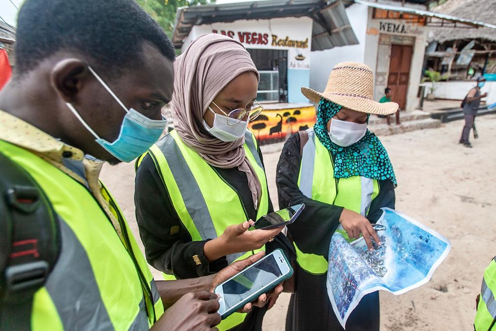 Three individuals (one male two female) wearing safety vests and masks looking at a map in a community street. Two of the individuals looking at the map also have phones.