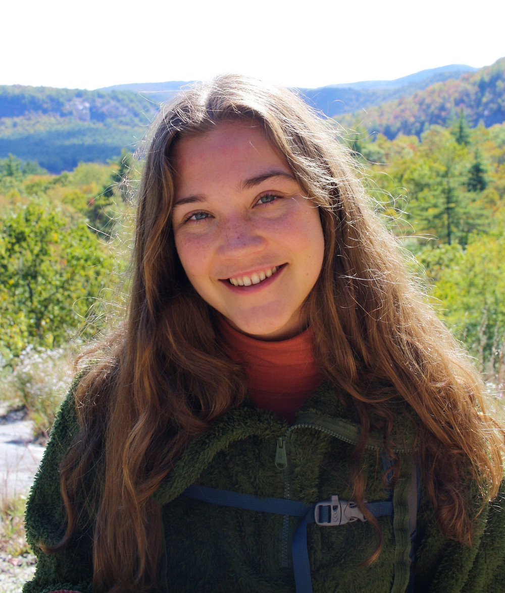 Photo of Noelle, female, with a mountain scape behind her in hiking attire.
