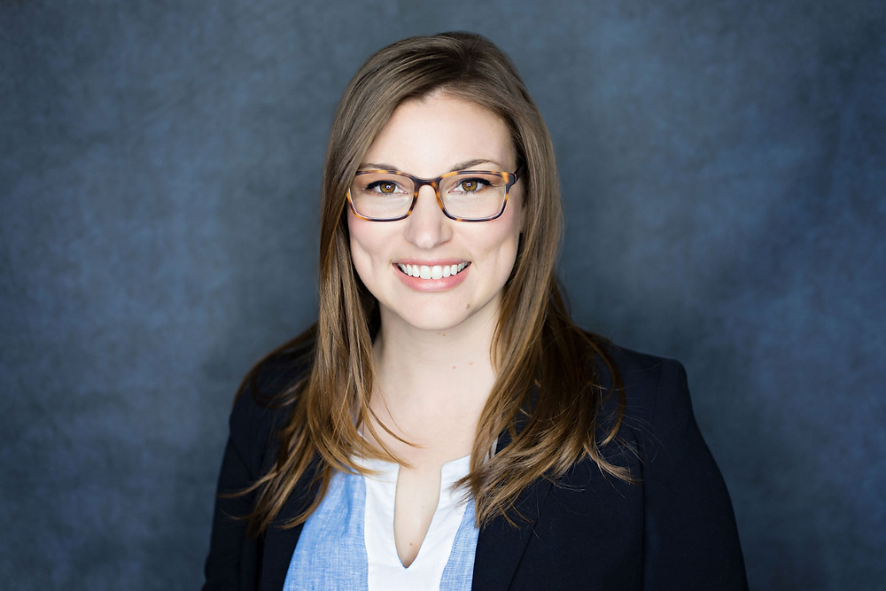Portrait image of women wearing black suit coat and glasses with blue background