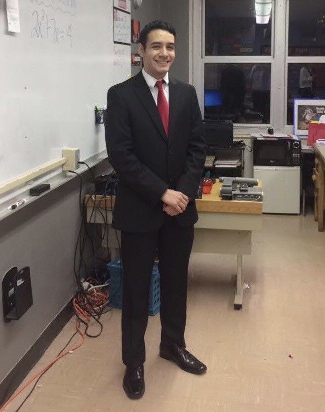 Male, Jesse, posing for photo in black suit with a red tie in a classroom.