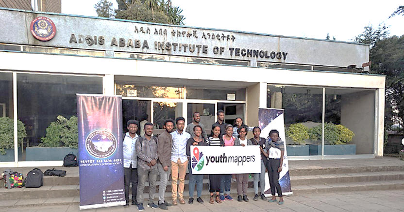 "Group of students in front of building titled ""Addis Ababa Institute of Technology"" holding a YouthMappers banner."