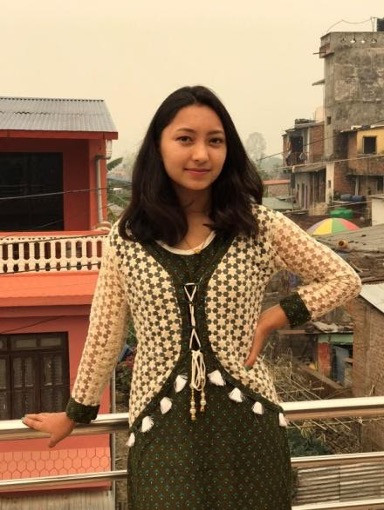 Portrait of women wearing white and green posing on a balcony with a city behind her.
