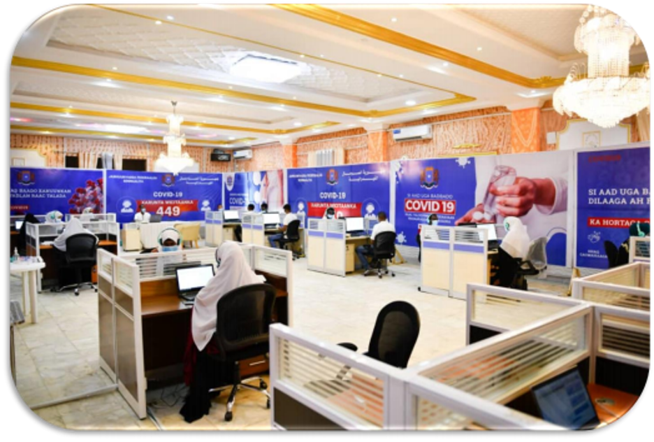Large room with large COVID-19 related flyers along the walls. There are several cubby desks with women and men sitting at computers.