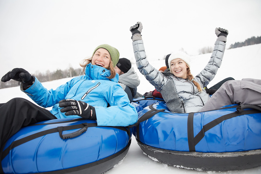 friends smile as they go snow tubing