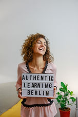 Picture of Despina, a German instructor smiling and holdinga sign that says Authentic Learning Berlin