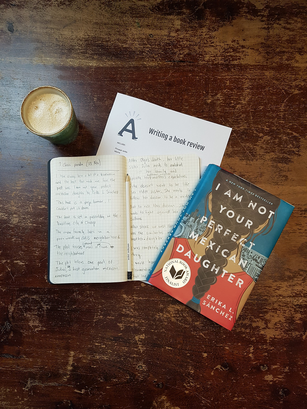 Image description: notebook with handwritten book review, a cup of coffee, and the book I am not your perfect Mexican daughter on a wooden table.
