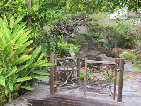gate made with branches found on site separates main deck from pond